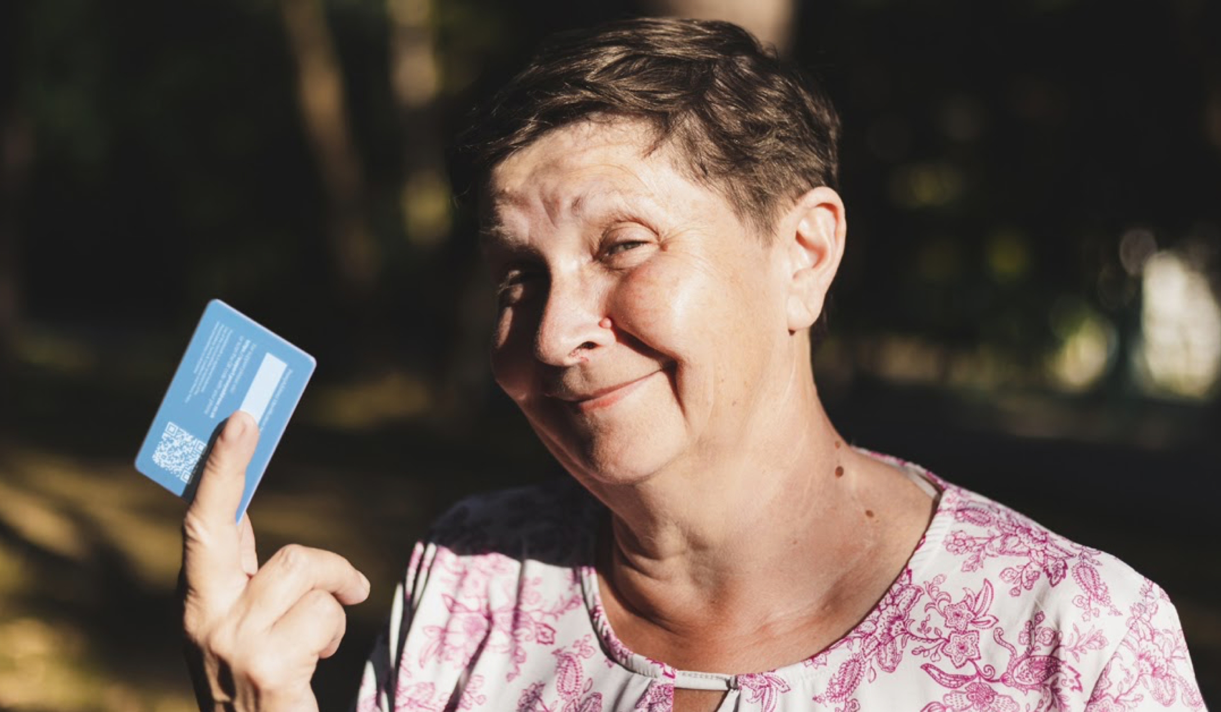 Smiling woman holds up blue ProxyAddress card